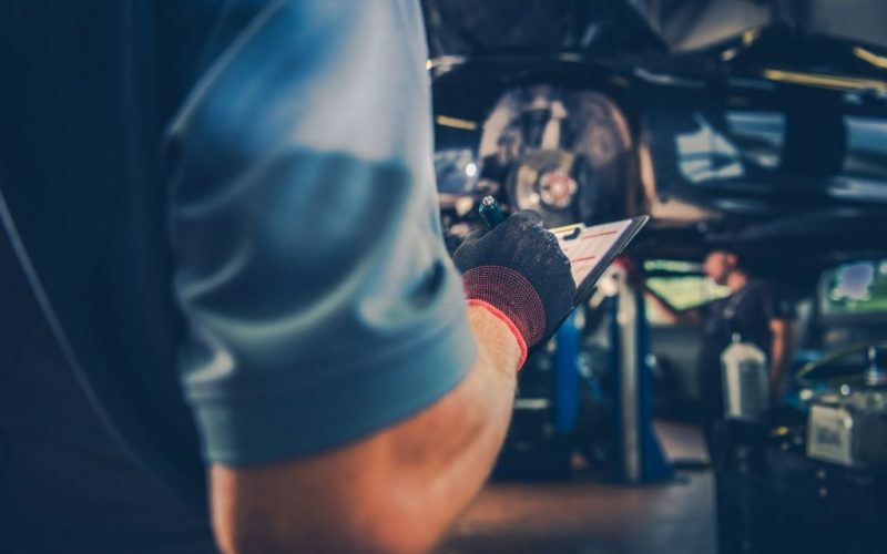 Vehicle Maintenance Check List. Car Mechanic with Documentation in Hand. Automotive Industry Theme.